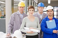 Business people and construction workers posing in office