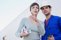 Businesswoman with blueprints talking to construction worker