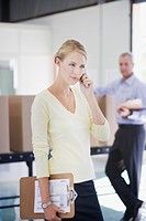 Businesswoman talking on cell phone in warehouse