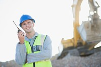 Construction worker talking on walkie_talkie on construction site