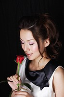 Woman with Closed Eyes Holding Red Rose