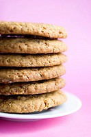 A stack of chocolate chip cookies on a white plate against a pink background