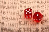 pair of dice sitting on share information in a copy of the financial times