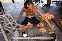 Thailand, Northeastern Thailand, Isan region, Chaiyaphum province, Ban Khwao, specialised centre in silk manufacture, man weaving silk threads with an...