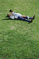Father and daughter lying together in grassy field