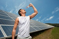 man drinking in front of solar panel