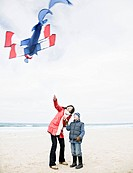 Woman & boy on beach with kite