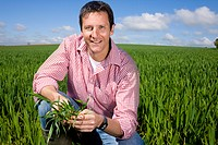 Smiling farmer crouching in field and examining young wheat crop