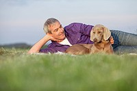 man with dog lying on the grass smiling