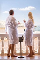 Couple in bathrobes drinking champagne on balcony