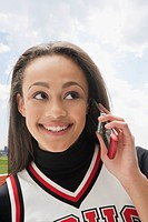 Mixed race cheerleader talking on cell phone