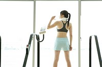 A woman takes a break while exercising as she drinks water (thumbnail)