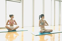 Two young women cross their legs and sit while they perform yoga in the gym
