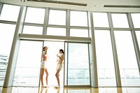 Two young women take a break from exercise as they drink water while standing near the sliding door