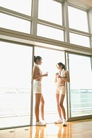 Two young women take a break from exercise as they stand near the sliding door