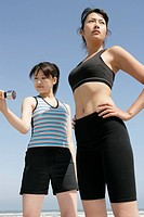 A young woman holds the dumbbell as her mate looks on