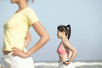 Two young women stand at the seashore with dumbbell in on of the womans hand