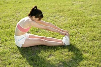 A young woman stretching her hands till her toes while exercising (thumbnail)
