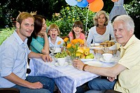 A multi_generational family having breakfast, outdoors