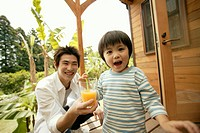 A small boy holding a straw as his father holds the glass of juice for him