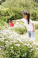 A young girl watering the flowers in the garden