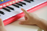 A child playing a toy organ