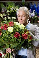 A woman smelling a bouquet of flowers in a florists