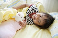 A girl in bed with a soft doll