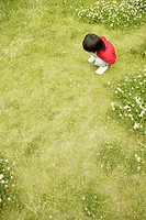 Small boy staring at the grass in the garden