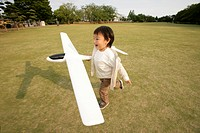 A small boy running on the ground as he holds an aeroplane in his hand