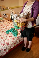 A young woman holds a basket full of clothes as she stands near the bed