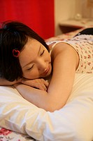 A young woman sleeps peacefully on the bed in a cozy bedroom