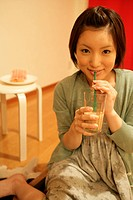 A young woman takes a sip from a glass as she smiles at the camera