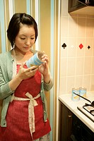 A young woman at kitchen, getting ready to cook (thumbnail)