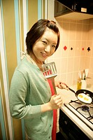 A young woman at kitchen, cooking the fried eggs (thumbnail)