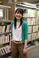 A young woman standing in front of the book shelves