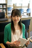 A young woman sits with a book in her hand as she smiles at the camera