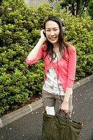 Young woman stands with her handbag while she puts her headphones on and listens to the music
