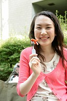 A young woman holds her food in the fork while she smiles at the camera