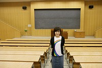 A young woman stands alone inside the classroom as she smiles at the camera