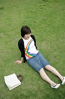 High angle view of a young woman relaxing on the grassland