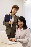 Two women faces the camera as one of them works on the laptop (thumbnail)
