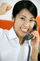 An ecstatic woman showing her emotions while conversing on the telephone
