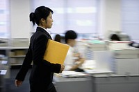 A side view of a woman holding a file moves on in the office