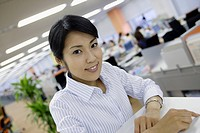 A woman sitting in her office smiles at the camera