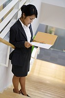 A businesswoman reading a file as she stands on the staircase