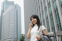 A woman seen conversing on the mobile phone amidst a commercial area