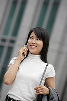 A woman smiling as she converses on the mobile phone