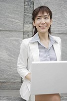 A woman working on her laptop smiles at someone (thumbnail)