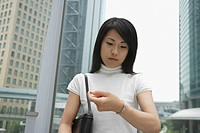 A woman looks over her watch near a commercial area